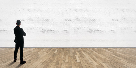 briks: Businessman stands opposite white bricks wall in gallery interior with wooden floor. Horizontal Stock Photo