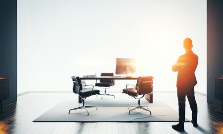 Homme d'affaires se trouve dans l'intérieur de bureau contemporain. Espace de travail en mezzanine avec ordinateur design générique, plancher en bois et vue panoramique sur la ville. Effets de bokeh