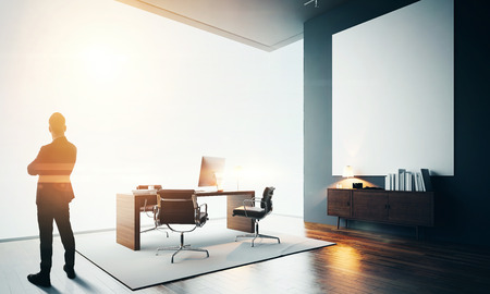 canvas: Business man stands in contemporary office interior. Worksplace in loft with generic design computer, wood floor and one empty canvas. Bokeh effects