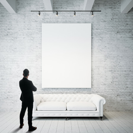 Człowiek stoi przed gospodarstwa puste białe płótno i klasyczne klasyczne sofa na drewnianą podłogę. Pionowy