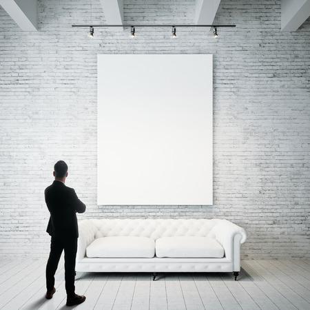 El hombre se opone a sostener el lienzo blanco en blanco y el sofá clásico vintage en el piso de madera. Vertical