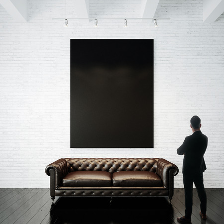 white wood floor: Man stands against holding blank white canvas and vintage classic sofa on the wood floor.