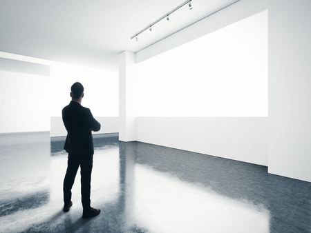 sign up: Businessman stands in contemporary gallery and looking at the white screen. Horizontal
