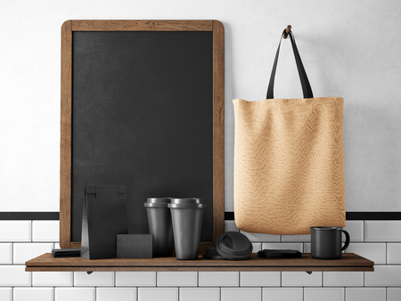 pockets: Black chalk board on bookshelf with two blank coffee cups, businesscards, coffee pocket and holding brown cotton bag. Horizontal Stock Photo