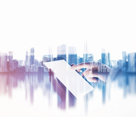 Girl touching screen of her tablet on the blurred city background. Double exposure, horizontal Stockfoto