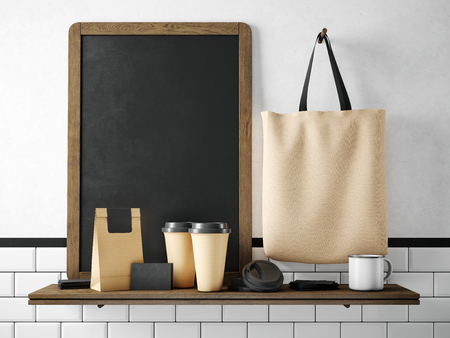 Black chalkboard on bookshelf with two blank coffee cups, businesscards, coffee pocket and holding cotton bag. Horizontal