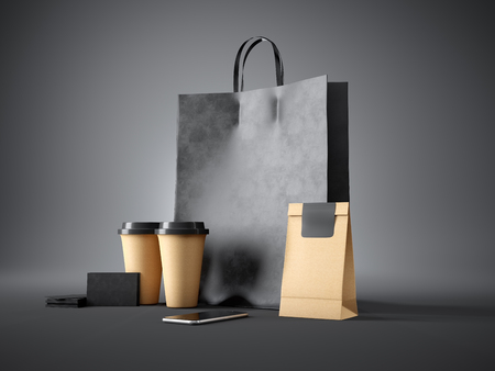 package design: Set of black shopping bag, two coffee cups, craft package, black business cards and generic design smartphone. Dark background