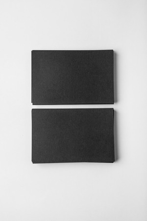 black shadows: Two stack of blank black business cards on white background with soft shadows.