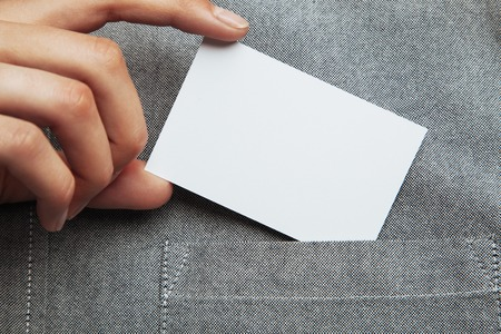 Closeup of man putting blank business card in his pocket of shirt. Horizontal Foto de archivo