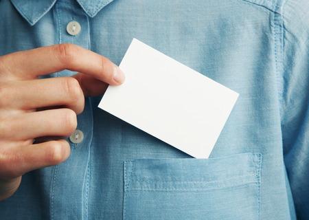 fondo para tarjetas: Joven hombre de negocios que lleva a cabo la tarjeta de visita en blanco del bolsillo de su camisa. Horizontal