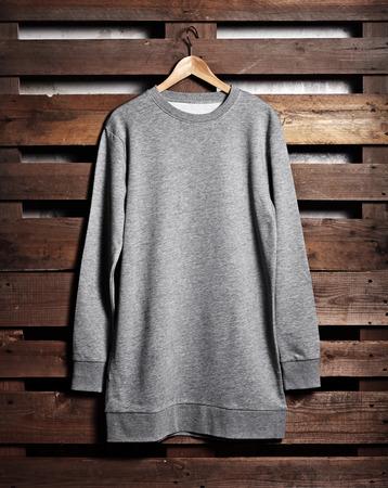 hoody: Photo of grey hoody hanging on wood background. Vertical