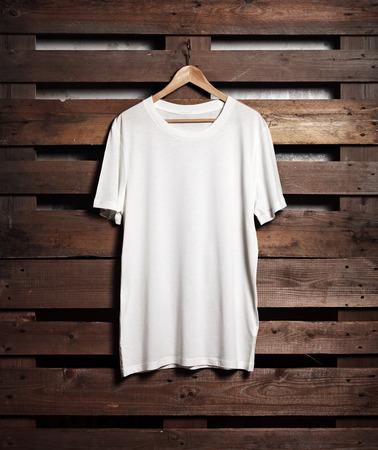 Foto von blanc weißes T-Shirt hängen auf Holz Hintergrund. Vertikal