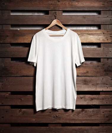 Photo of blanc white tshirt hanging on wood background. Vertical Imagens
