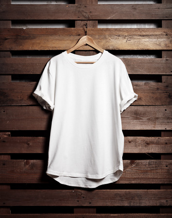 Picture of blanc white tshirt hanging on wood background. Vertical