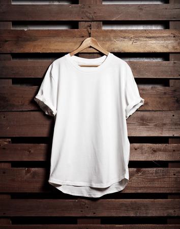 Immagine di blanc maglietta bianca appesa sullo sfondo di legno. Verticale