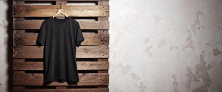 Foto di nero tshirt appeso di fronte a sfondo legno. Ampio, ombre morbide.