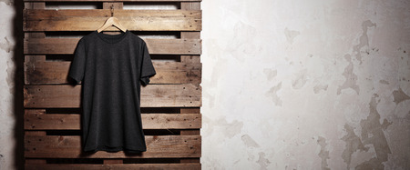 body shop: Photo of black tshirt  hanging in front of wood background. Wide, soft shadows. Stock Photo
