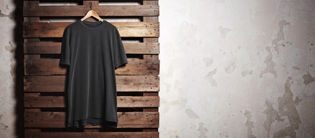 fashion background: Photo of black tshirt  hanging in front of concrete wall. Wide, soft shadows.