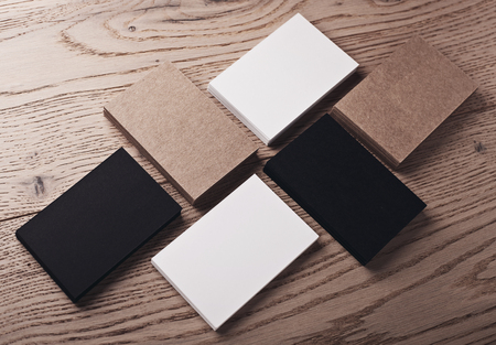 wood craft: Photo of white, black and craft business cards on natural wood table.