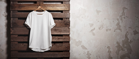 store sign: Photo of white tshirt  hanging in front of concrete wall. Wide, soft shadows.
