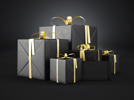 Set of black gift boxes of various sizes with golden ribbon bow and blank envelope  on dark background.