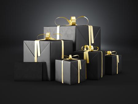 Conjunto de cajas de regalo negro de diferentes tamaños con lazo de cinta de oro y dos sobres en blanco sobre un fondo oscuro. Foto de archivo