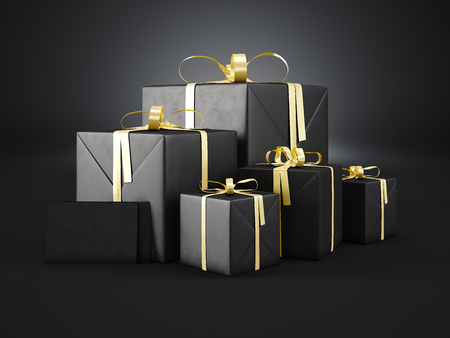 Set of black gift boxes of various sizes with golden ribbon bow and two blank envelope  on dark background.