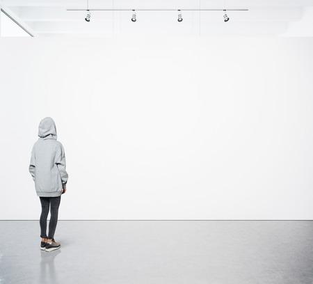 arte moderno: Mujer joven que recorre en la galería de moderno y mirando el lienzo en blanco.