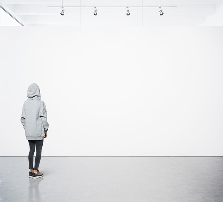 Young woman walking in modern gallery and looking at the blank canvas. Stok Fotoğraf