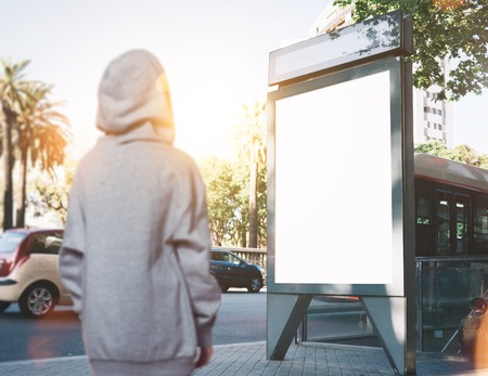 blurred people: Photo of girl looking at blank lightbox on the bus stop.