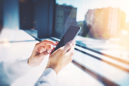 cell phones: Girl touching a screen of her smarthone. Blurred background Stock Photo