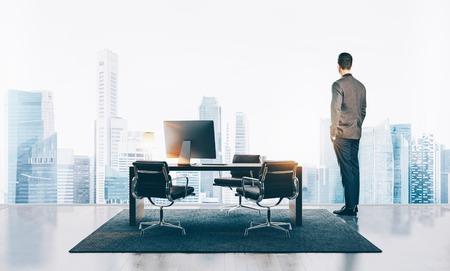 ejecutivo en oficina: El hombre de negocios lleva traje moderno y mirando a la ciudad en la oficina contemporánea. Horizontal