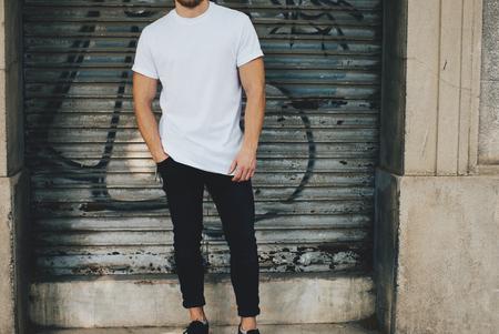 modelo: Foto de un hombre con barba que llevaba camiseta en blanco, vaqueros negros y de pie enfrente del garaje