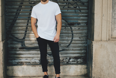Photo of a bearded man wearing blank t-shirt, black jeans and standing opposite garage Stock Photo