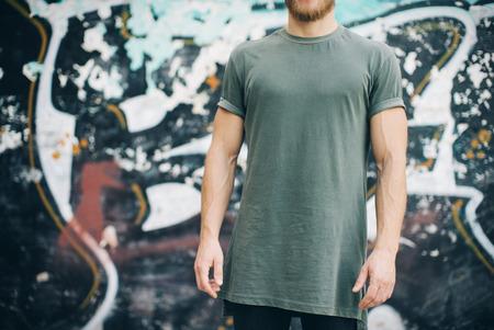 ragazzo barbuto indossando t-shirt bianca e jeans neri verdi, in piedi sulla strada. Archivio Fotografico