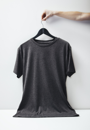 Foto di Blanc maglietta nera appesa su sfondo bianco. Verticale