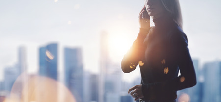 mobile business: Portrait of young woman holding her smartphone in a hands. Blurred city on the background.