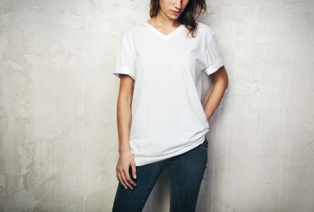 Jeune fille portant t-shirt blanc et un jean noir. Béton fond mur. Horizontal