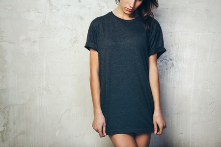 Young girl wearing blank black t-shirt. Concrete wall background