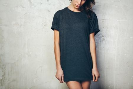 camisa: Niña llevaba en blanco negro de la camiseta. Fondo de la pared de concreto