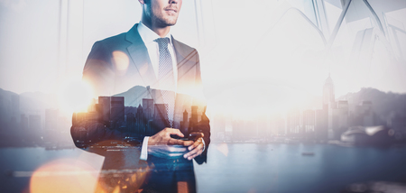 career: Photo of businessman holding smartphone. Double exposure photo of panoramic city view at sunrise
