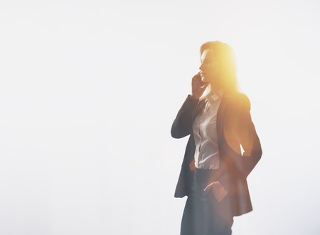blurred people: Young woman wearing modern suit, talking on smartphone. Isolated. Horizontal