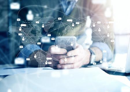 tecnologia: conceito de negócio, homem de negócios que usa o smartphone. Plantas arquitectónicas na mesa. interface de conexão digital
