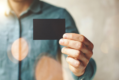 business symbols: Man wearing blue jeans shirt and showing blank black business card. Blurred background. Horizontal