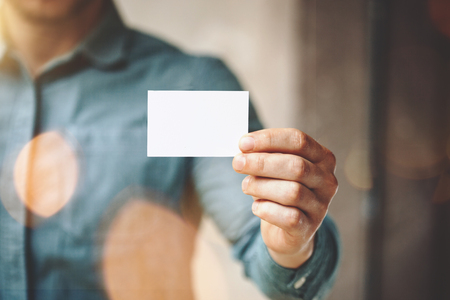Man wearing blue jeans shirt and showing blank white business card. Blurred background. Horizontal