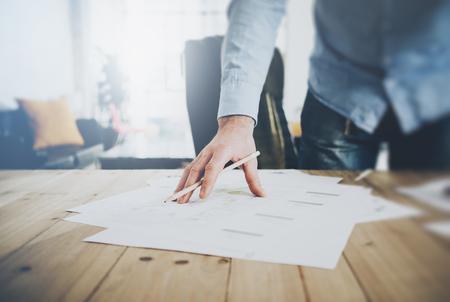 El hombre de negocios en el trabajo. Sostiene un lápiz en la mano. proyecto arquitectónico en la mesa.