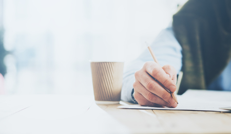 hombre escribiendo: El hombre de negocios lápiz de entrega y el proyecto de nuevo negocio portátil de trabajo. Genérico portátil de diseño sobre la mesa. fondo borroso