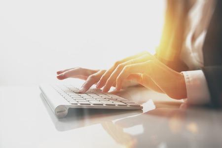 Nahaufnahme Foto der weibliche Hände Eingabe von Text auf einer Tastatur. Visuelle Effekte, weißen Hintergrund.