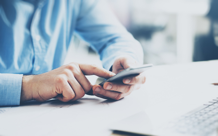 business office: Businessman typing text smartphone. Generic design laptop on the table. Blurred background