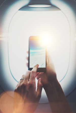 clouds making: Photo of female hands making foto of clouds on smartphone. Visual effects, blurred. Stock Photo